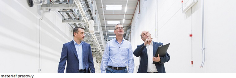 Three businessmen inspecting corridor in factory