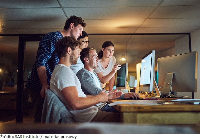 Shot of a group of young people using a computer together during a late night in a modern office